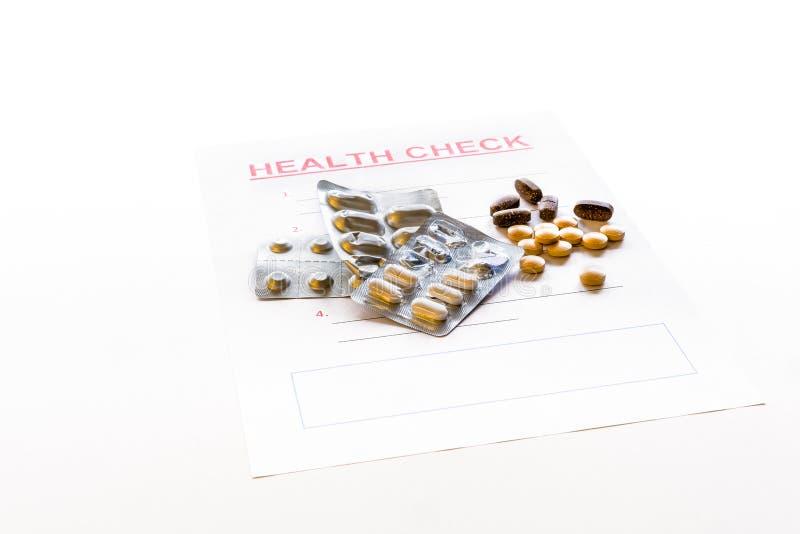 Una forma in bianco del controllo sanitario con medicina, le vitamine, le pillole e l'imballaggio sparsi su  immagini stock libere da diritti
