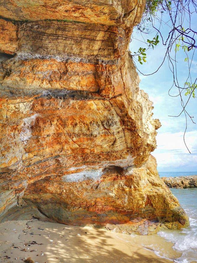 Una formación de roca hermosa y una reflexión lisa sedosa del agua en la playa foto de archivo