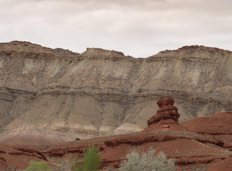 Una formazione rocciosa rossa nodosa con Gray Cliffs Behind fotografie stock