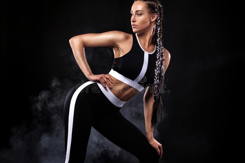 Una forte donna atletica su fondo nero che dura nella motivazione nera degli abiti sportivi, di forma fisica e di sport Concetto  fotografia stock