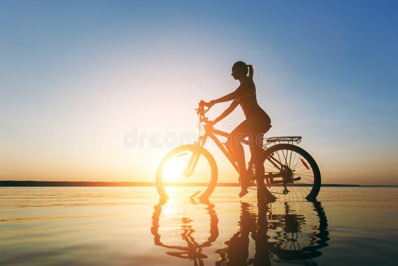 Una forte donna bionda in un vestito variopinto si siede sulla bicicletta nell'acqua al tramonto un giorno di estate caldo Concet fotografie stock