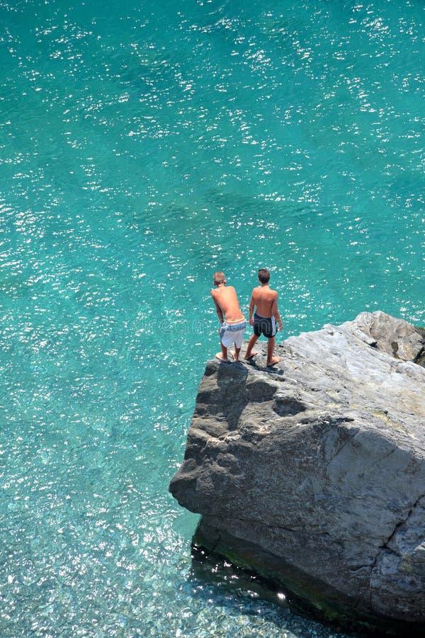 Una foto aerea di due giovani ragazzi sulla roccia che esamina il mare fotografia stock libera da diritti
