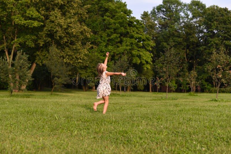 Una foto calda di una bambina che esegue piede nudo su un'erba verde immagine stock libera da diritti
