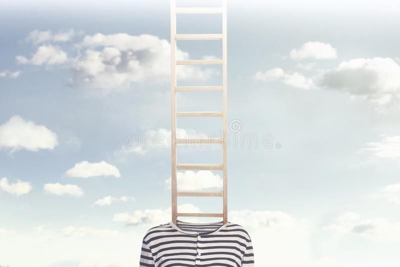 Una foto concettuale con una scala che esce da un corpo del ` s della persona e che scala verso un cielo nuvoloso fotografia stock libera da diritti