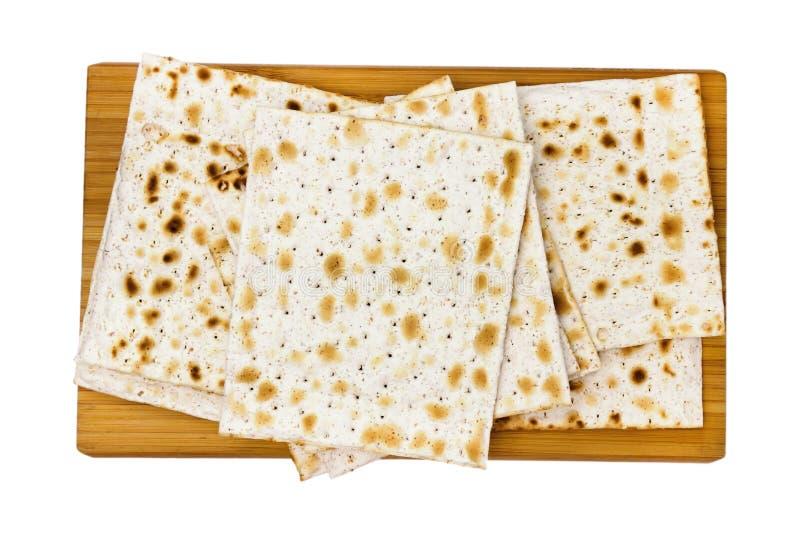 Una foto de arriba del matza judío en la tajadera de madera, pan leudado aislado en el fondo blanco La foto desde arriba foto de archivo libre de regalías
