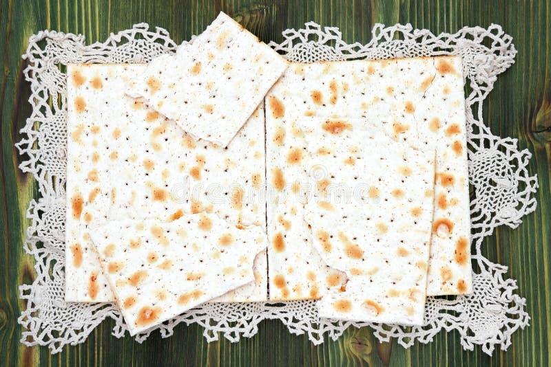 Una foto de arriba del matzah o del pedazo del matza en el tapetito del cordón Matzah en la tabla de madera para los días de fies imagenes de archivo