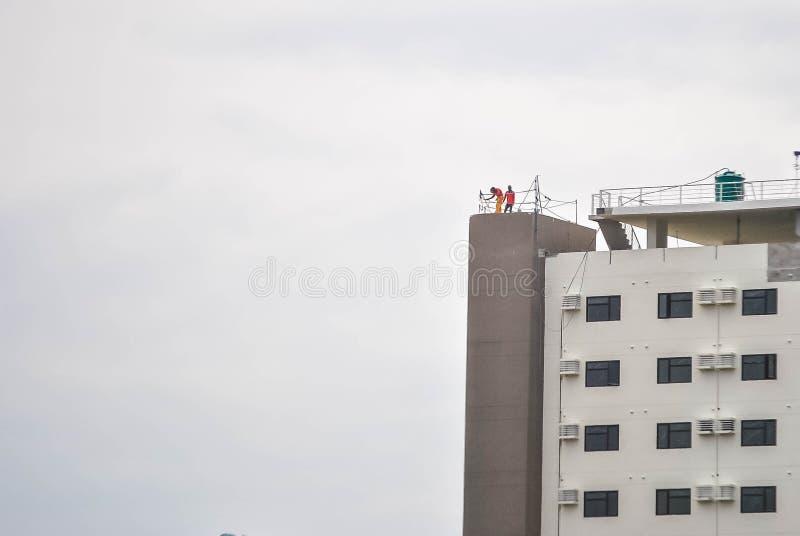 Una foto de los hombres que trabajan en la cubierta del tejado imagen de archivo libre de regalías