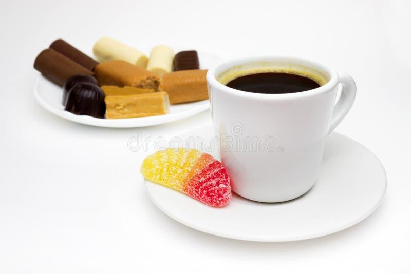 Una foto de su taza de café blanca de la porcelana, caramelo de azúcar amarillo y rojo colorido de la fruta cítrica de la jalea d fotos de archivo libres de regalías