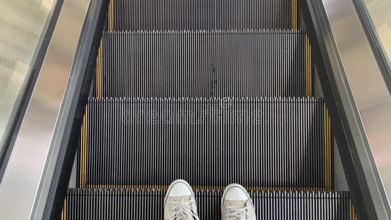 Una foto del pie mientras que camina abajo de la escalera móvil imagenes de archivo