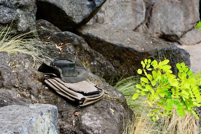 Una foto del primer de un sombrero de vaquero resistido viejo y de un bolso del viaje, dejada en piedra en el salvaje imagen de archivo