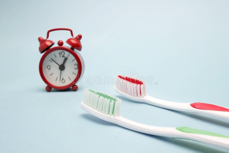 Una foto della sveglia rossa e di due spazzolini da denti Tempo di pulire i denti Cure odontoiatriche, foto di concetto di igiene fotografia stock