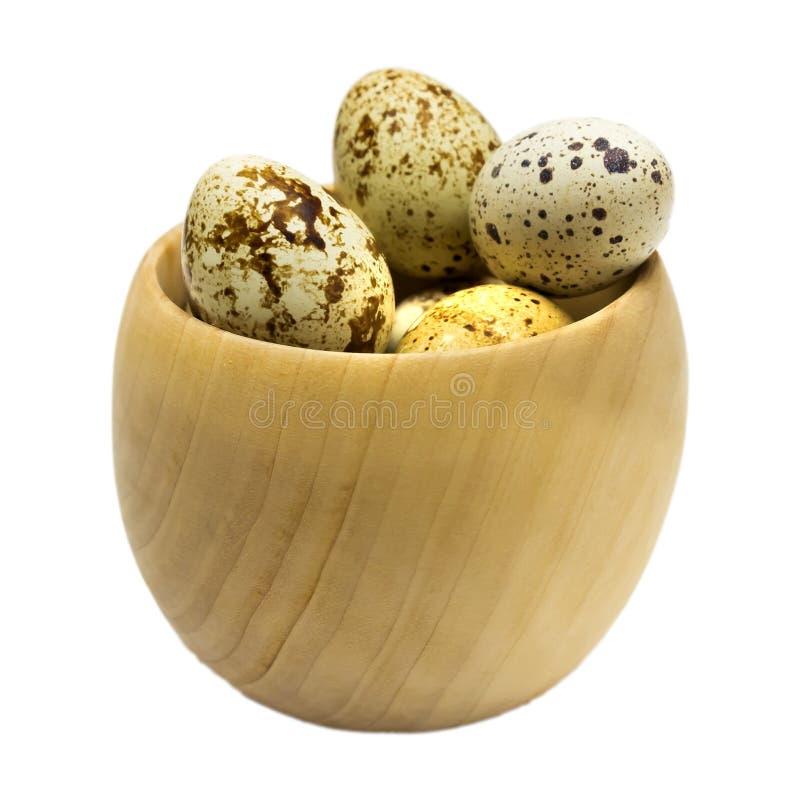 Una foto di alcune uova fresche della quaglia cruda in ciotola di legno isolata su bianco Gradisco lo stile di vita sano, concett immagini stock