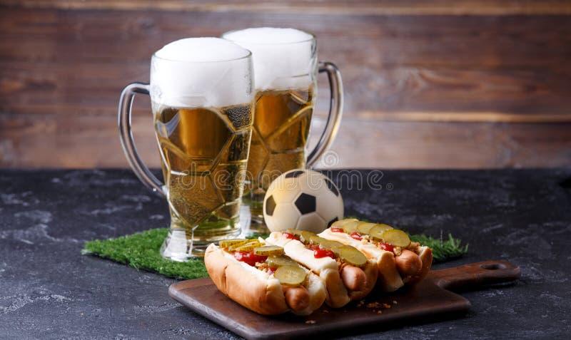 Una foto di due tazze della birra della schiuma, erba verde con calcio, hot dog fotografia stock libera da diritti