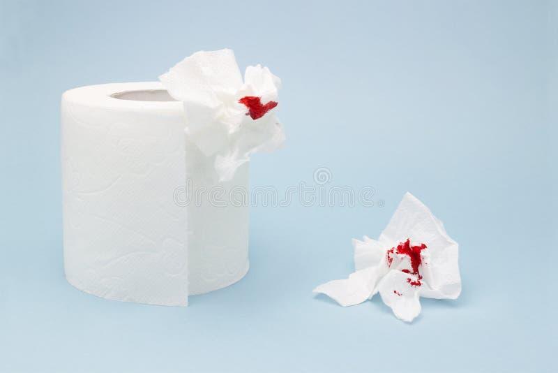 Una foto di un rotolo della carta igienica e due hanno usato gli strati sanguinosi della carta igienica Gocce e tracce del sangue immagine stock libera da diritti