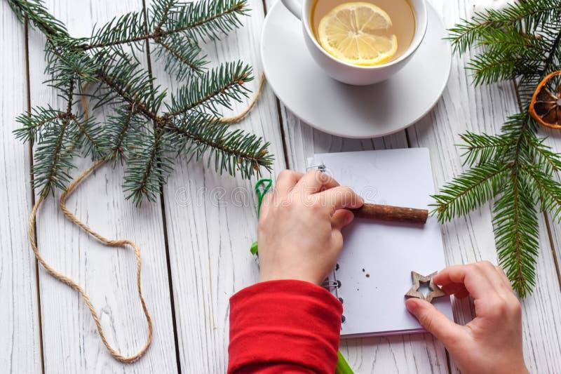 Una foto festiva de un par de las manos de los niños que embalan los regalos de la Navidad fotos de archivo libres de regalías