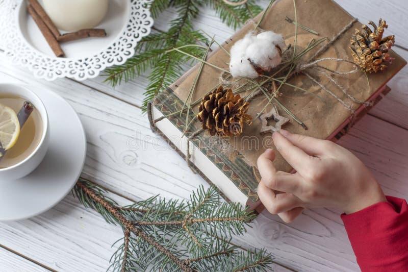 Una foto festiva de un par de las manos de los niños que embalan los regalos de la Navidad imagen de archivo