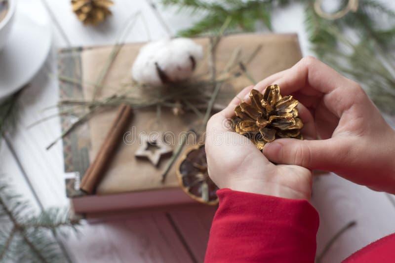 Una foto festiva de un par de las manos de los niños que embalan los regalos de la Navidad fotos de archivo