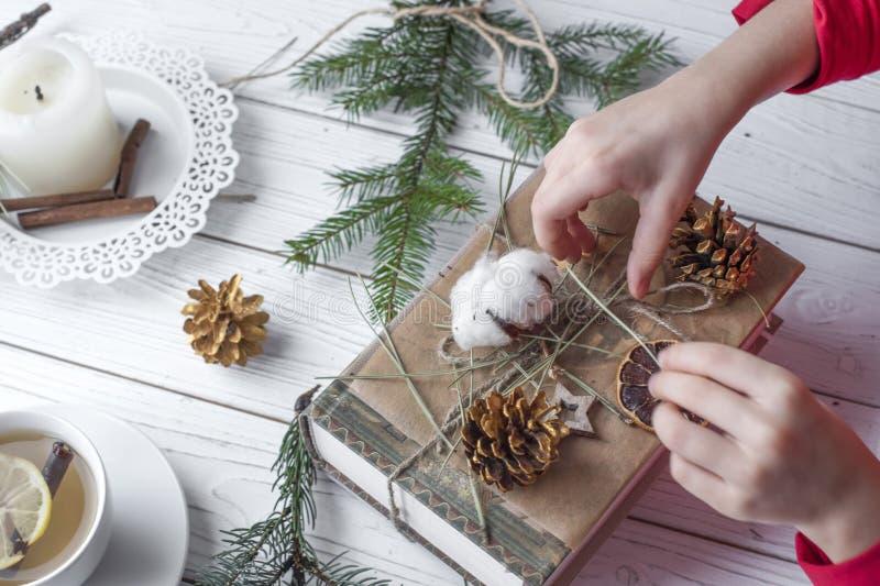 Una foto festiva de un par de las manos de los niños que embalan los regalos de la Navidad imagen de archivo libre de regalías