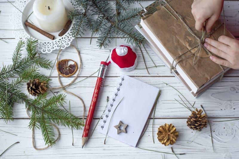 Una foto festiva de un par de las manos de los niños que embalan los regalos de la Navidad imágenes de archivo libres de regalías