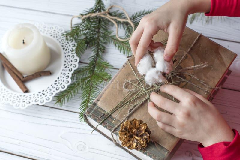 Una foto festiva de un par de las manos de los niños que embalan los regalos de la Navidad fotografía de archivo libre de regalías