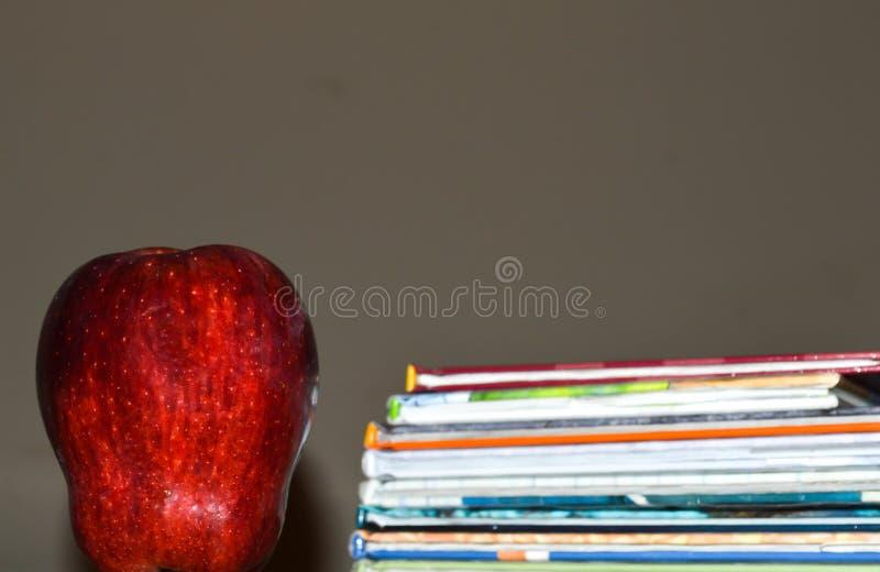 Una foto oscura de una manzana al lado de una pila de libro del ` s de los niños para la educación imagen de archivo