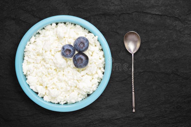 Una foto sopraelevata della ricotta naturale fresca con i mirtilli e un cucchiaio d'argento in una ciotola ceramica blu sulla pie fotografia stock