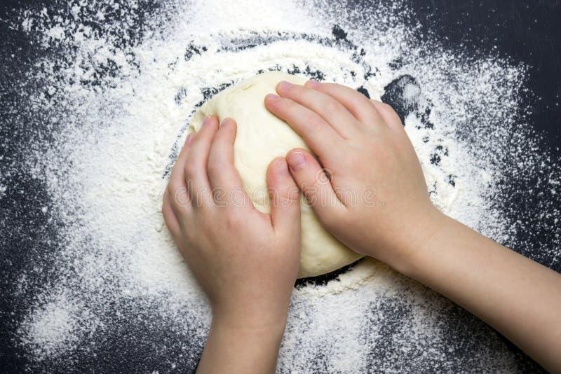 Una foto sopraelevata delle mani del ` s del bambino, di una certa farina spruzzata e della pasta del grano sulla tavola nera con immagini stock libere da diritti