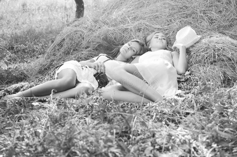 Una fotografia bianca nera di due ragazze felici che si trovano sul fieno fresco e sul primo piano di conversazione di segreti fotografia stock
