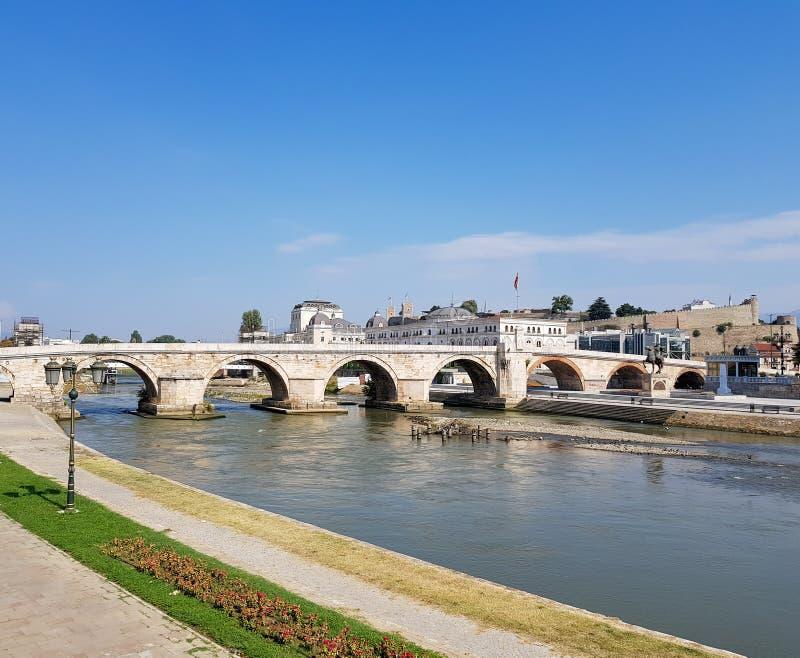 Una fotografia del fiume che passa sotto il ponte di pietra fotografia stock