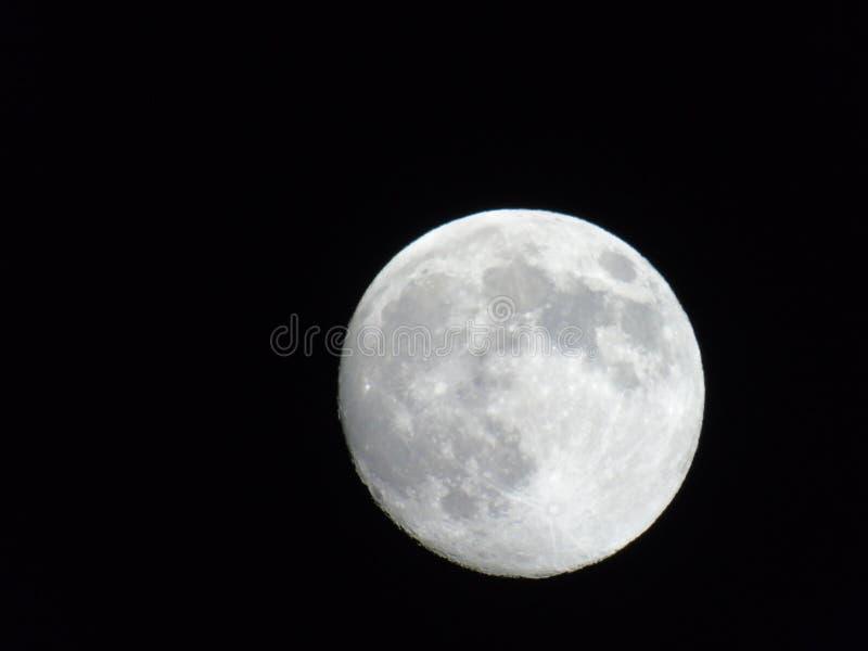 Una fotografia stupefacente della luna piena sopra la città immagini stock