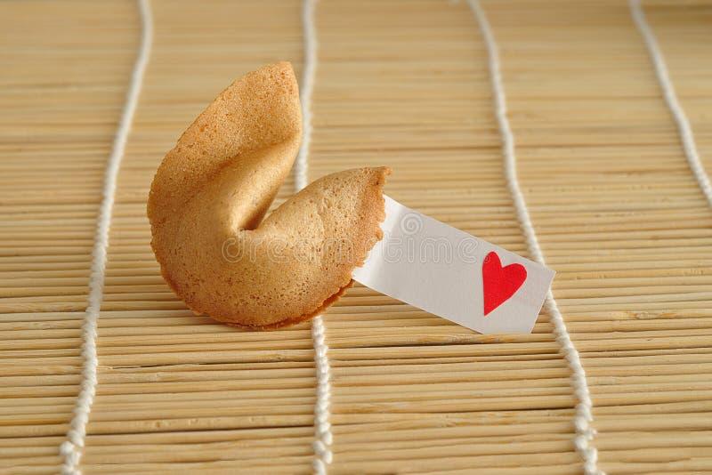 Una galleta de la suerte con un trozo de papel y un corazón rojo foto de archivo libre de regalías