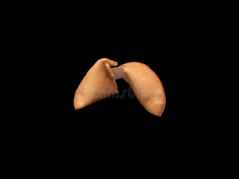Una galleta de la suerte en fondo negro fotografía de archivo libre de regalías