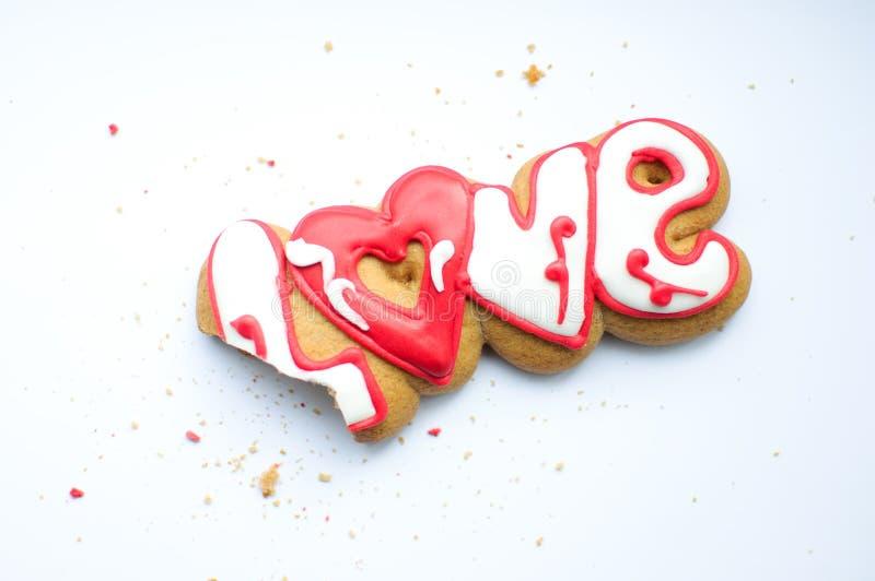 Una galleta mordida para el día del ` s de la tarjeta del día de San Valentín o para un día y las migas de boda en un fondo blanc fotos de archivo libres de regalías