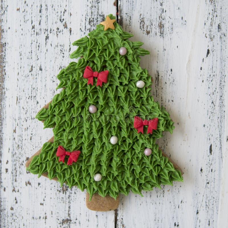 Una galleta verde del pan de jengibre de la Navidad del esmalte en la forma del árbol de Chrismas en una tabla de madera blanca C foto de archivo