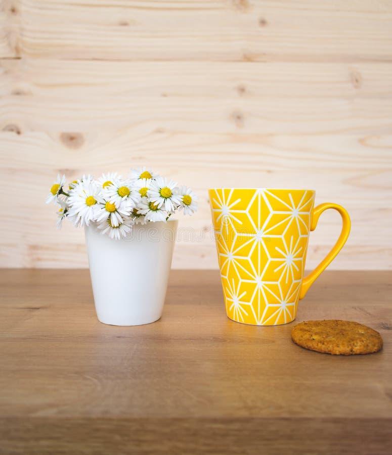 Una galleta y una taza de caf? amarilla y un manojo de margaritas en el fondo imágenes de archivo libres de regalías