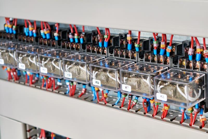 Una gama de retransmisiones intermedias eléctricas en un gabinete eléctrico imágenes de archivo libres de regalías