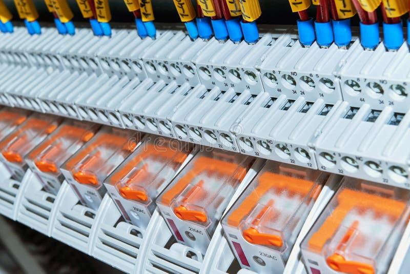 Una gama de retransmisiones intermedias en el gabinete eléctrico imagen de archivo
