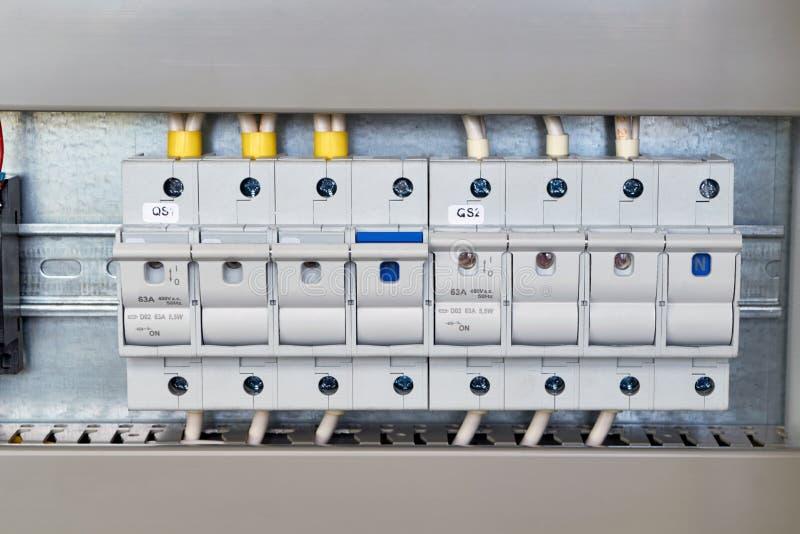 Una gama de tenedores o de desenganches del fusible en un gabinete eléctrico fotografía de archivo