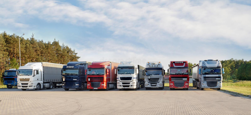 Una gama larga de diversos tipos y colores de camiones en un st del camión imagen de archivo