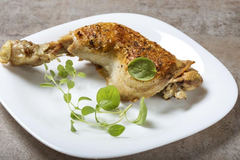 Una gamba di pollo fritto con le foglie verdi dell'origano fotografie stock