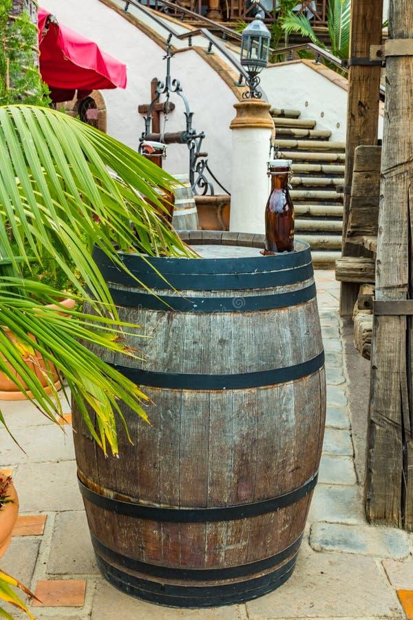 Una garrafa de soportes de cristal oscuros en un barril de vino del roble del vintage en un invernadero de Tenerife, islas Canari fotografía de archivo