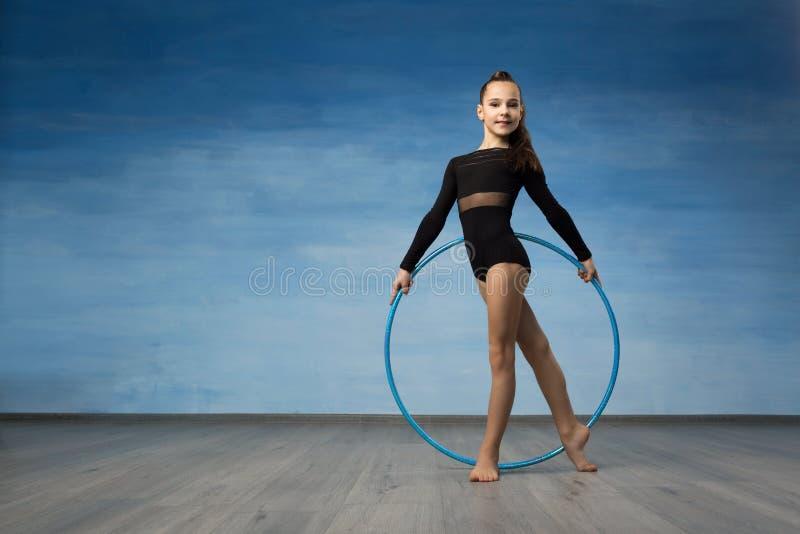 Una ginnasta della ragazza in un costume da bagno nero guarda nel profilo nelle mani di un cerchio relativo alla ginnastica immagini stock