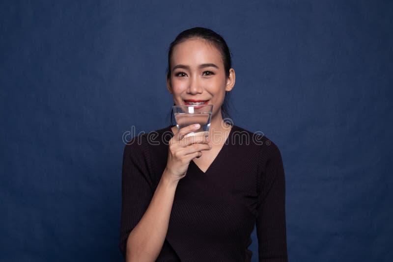Una giovane asiatica con un bicchiere d'acqua potabile fotografie stock