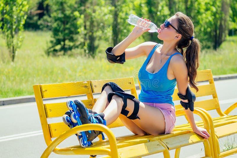 Una giovane atletica donna brunetta in pantaloncini rosa e blu con protesi al gomito e rospi al ginocchio fotografia stock