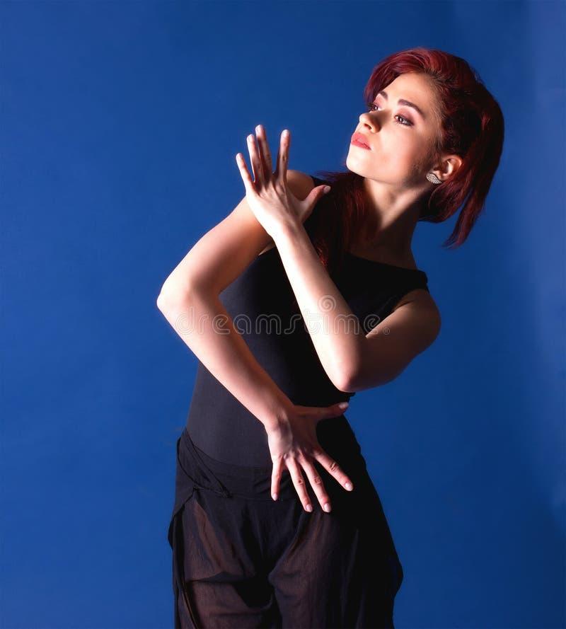 Una giovane ballerina in una bella posa su un fondo blu immagini stock