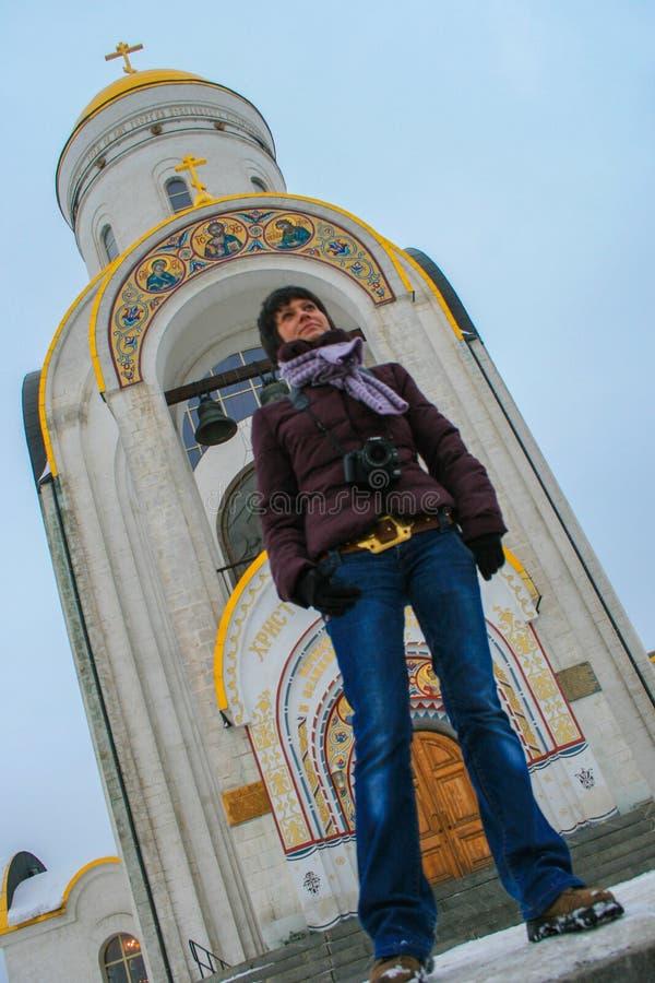 Una giovane bella condizione della donna sul fondo della chiesa nel parco di inverno fotografia stock libera da diritti