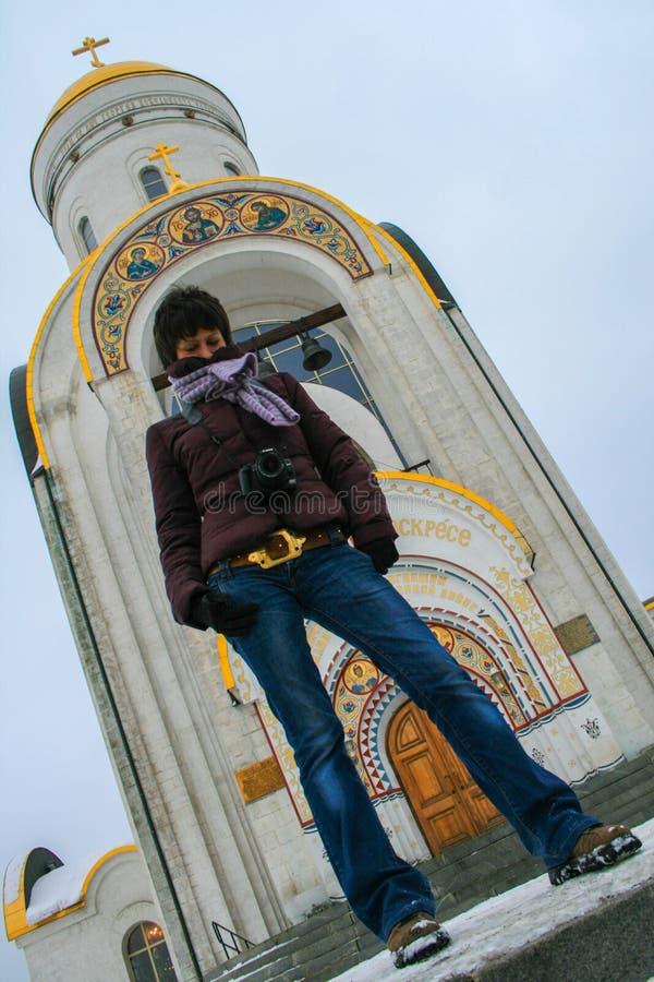 Una giovane bella condizione della donna sul fondo della chiesa nel parco di inverno immagine stock libera da diritti