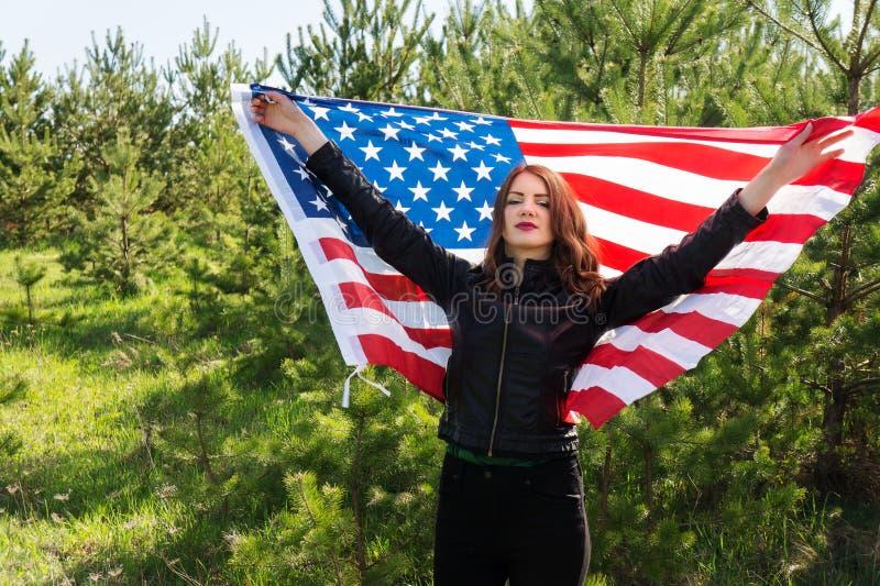 Una giovane bella donna con una bandiera degli Stati Uniti d'America fotografie stock