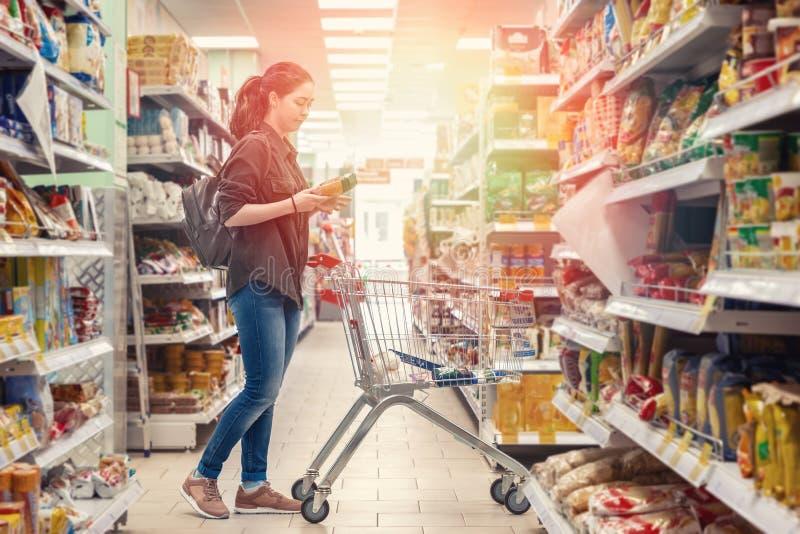 Una giovane bella donna rotola un carretto della drogheria e sceglie i prodotti nel supermercato luce fotografia stock