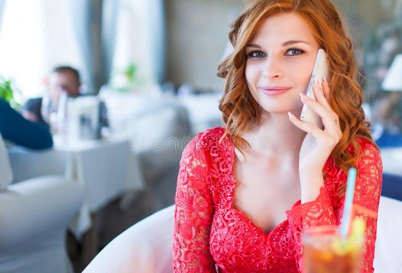 Una giovane bella donna sta bevendo il caffè in un caffè fotografie stock